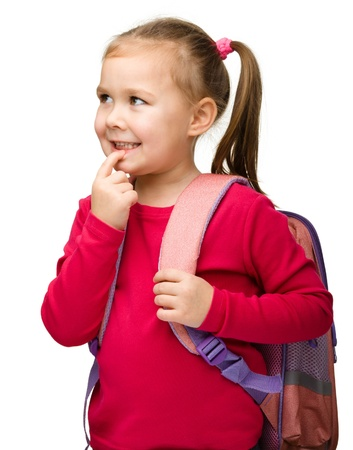 Portrait of a cute little schoolgirl with backpack thinking about something, isolated over white photo