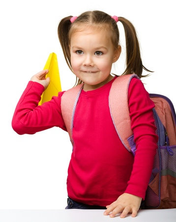 Portrait of little schoolgirl with backpack throwing a paper airplane, isolated over white Stock Photo - 13791438
