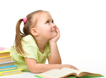 little table: Cute cheerful little girl is dreaming while reading books, isolated over white Stock Photo