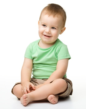 Portrait of a cute cheerful little boy, who is smiling while sitting on floor, isolated over white Stock Photo - 13791410
