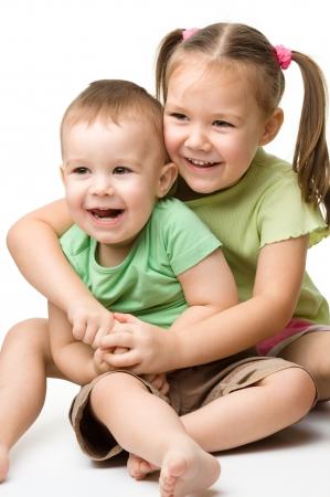 hermanos jugando: Dos hijos (una niña y un niño) se divierten mientras se está sentado en el suelo, aislado más de blanco Foto de archivo