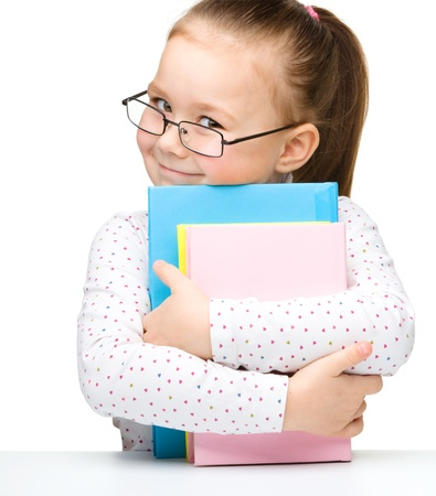 reading glasses: Cute cheerful little girl with books, isolated over white