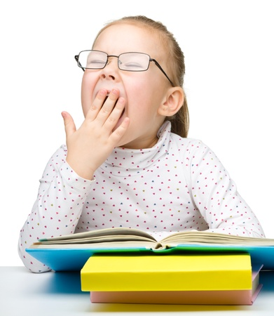 yawning: Cute cheerful little girl yawning while reading book and wearing glasses, isolated over white