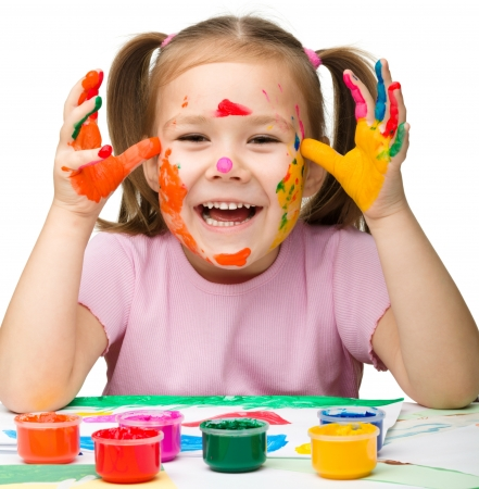 play of color: Portrait of a cute cheerful girl with painted hands, isolated over white