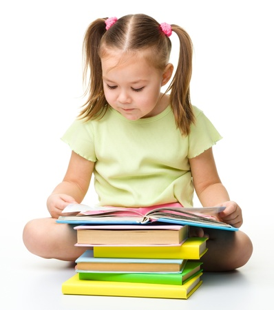 kids reading: Cute little girl reads a book, isolated over white