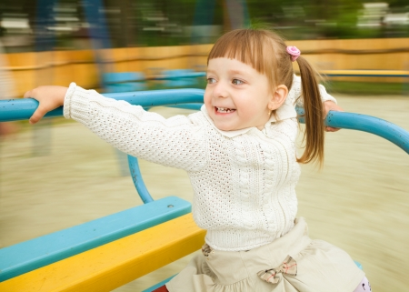 merry go round: Cute cheerful little girl is riding merry-go-round, background blurred with motion