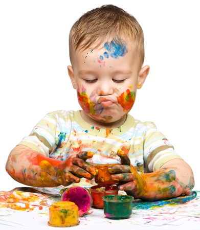 Portrait of a cute little boy messily playing with paints while making funny grimace, isolated over white Stock Photo - 14242073