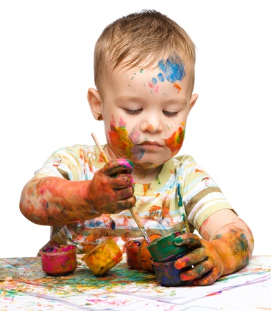 Portrait of a cute little boy messily playing with paints, isolated over white Stock Photo - 14242110