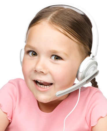 Closeup portrait of cute little girl tackling to customers as a consultant using headset, isolated over white photo