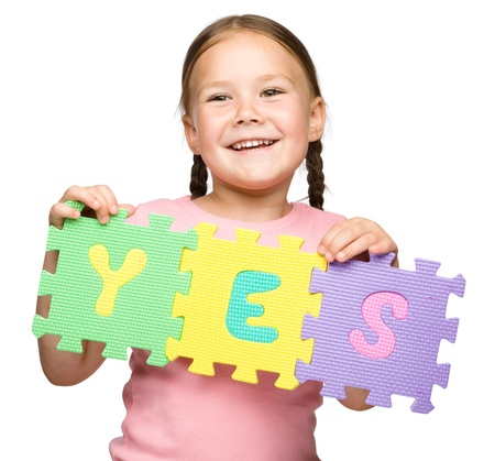 agreeing: Cute little girl is holding Yes slogan, isolated over white