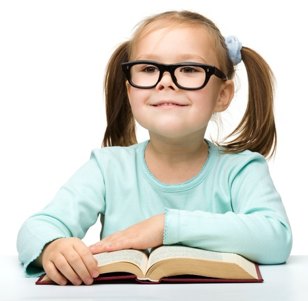 Happy little girl with book wearing black glasses, back to school concept, isolated over white