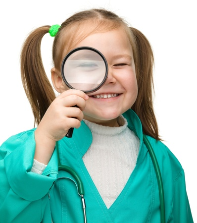 Cute little girl is playing doctor looking through magnifier, isolated over white Stock Photo - 14350472