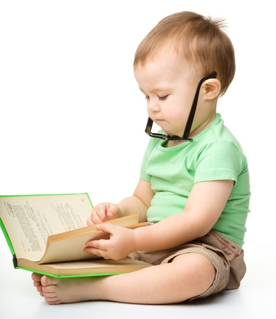boy book: Cute little boy reads a book, isolated over white