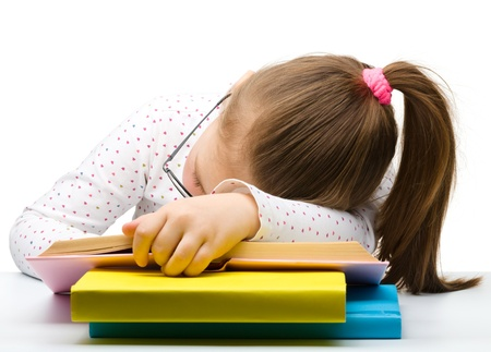 Cute little girl is sleeping on a book while wearing glasses, isolated over white Imagens