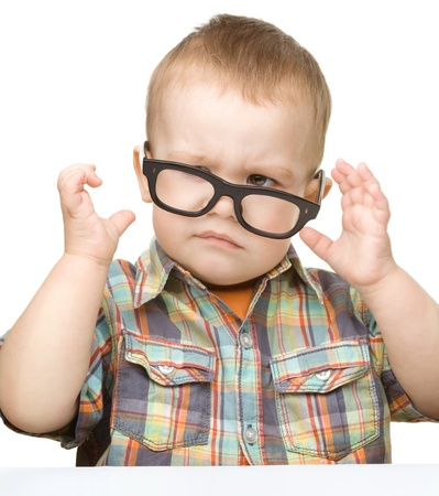 funny glasses: Portrait of a cute little boy wearing glasses and making funny grimace, isolated over white