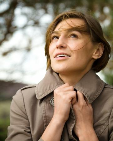 pale colours: Portrait of a happy beautiful woman in autumn park, pale colors