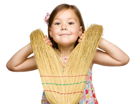 Portrait of a cute little girl with broom, isolated over white photo