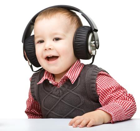 Cute little boy enjoying music using headphones, isolated over white Stock Photo