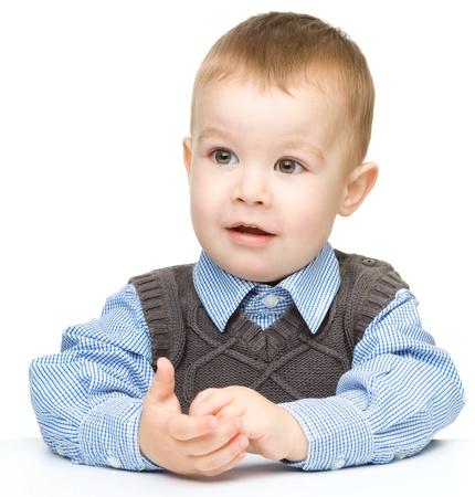 astonishment: Retrato de un ni�o lindo y con la boca abierta de asombro que apoyan su cabeza con la mano, aislados en blanco