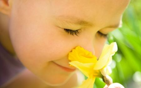 Retrato de una niña linda al aire libre, oliendo las flores
