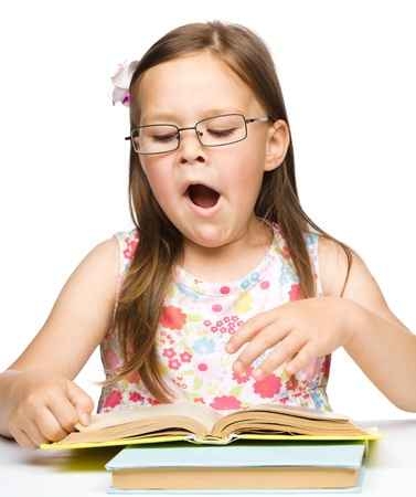 yawning: Cute little girl is yawning while reading book and wearing glasses, isolated over white