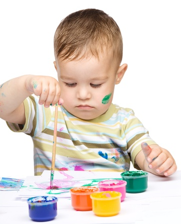 Portrait of a cute little boy playing with paints, isolated over white Stock Photo - 14589883