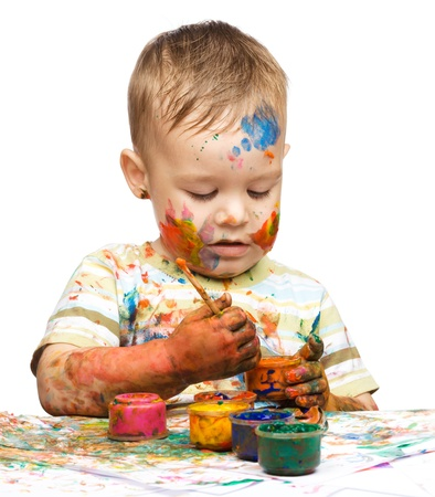 Portrait of a cute little boy messily playing with paints, isolated over white Stock Photo - 14589882