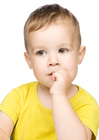 Portrait of a cute little boy looking at something while biting fingers, isolated over white photo
