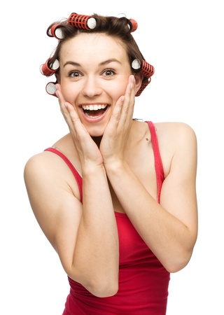 Young woman is holding her face in astonishment while wearing hair-rollers, isolated over white photo