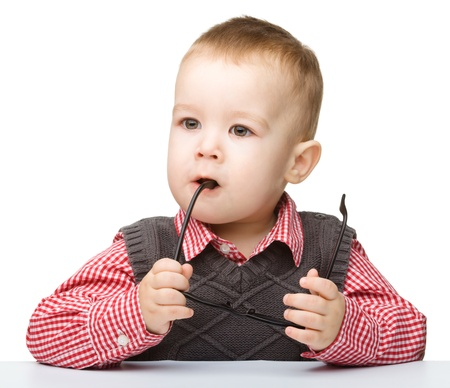 baby sit: Cute little child play with book and biting glasses while sitting at table, isolated over white