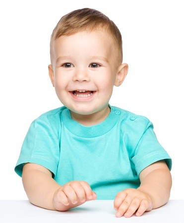 Portrait of a cute cheerful little boy, who is smiling while sitting at table, isolated over white photo