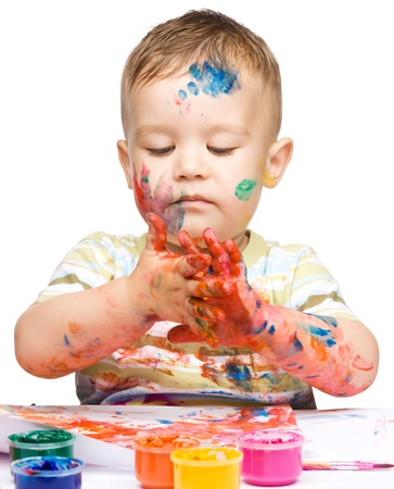 Portrait of a cute little boy messily playing with paints, isolated over white Stock Photo - 15335146