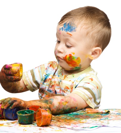 messily: Portrait of a cute little boy messily playing with paints, isolated over white