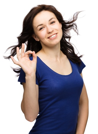 ok sign: Young woman dressed in blue is showing OK sign, isolated over white