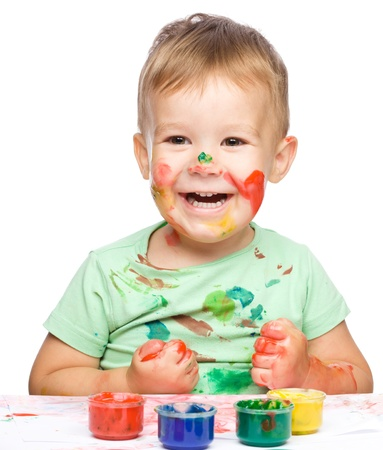 Portrait of a cute little boy playing with paints clenching his fists in joy, isolated over white Stock Photo - 15335180