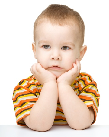 Portrait of a cute little boy looking at something while supporting his head with both hands, isolated over white photo