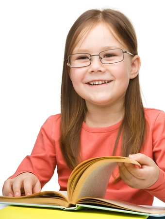 Cute cheerful little girl reading book wearing glasses, isolated over white Stock Photo - 15368622