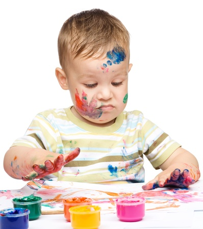 messily: Portrait of a cute little boy messily playing with paints making funny grimace, isolated over white