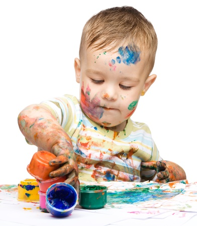 Portrait of a cute little boy messily playing with paints, isolated over white Stock Photo - 15368586