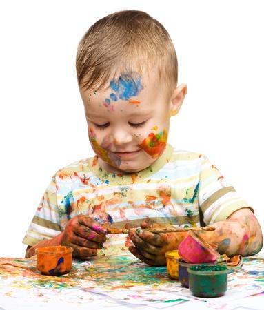 divertirsi: Ritratto di un ragazzo carino disordinato giocando con colori, isolato su bianco