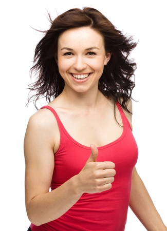 Young woman dressed in red is showing thumb up gesture, isolated over white photo