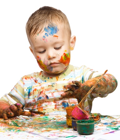 Portrait of a cute little boy messily playing with paints, isolated over white Stock Photo - 15531135