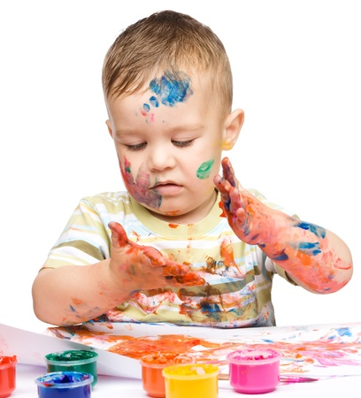 Portrait of a cute little boy messily playing with paints, isolated over white Stock Photo - 15940411