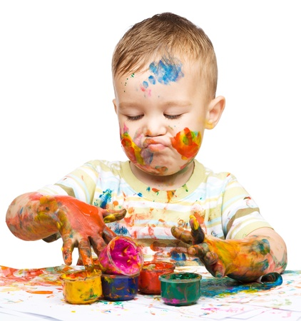 messily: Portrait of a cute little boy messily playing with paints while making funny grimace, isolated over white Stock Photo