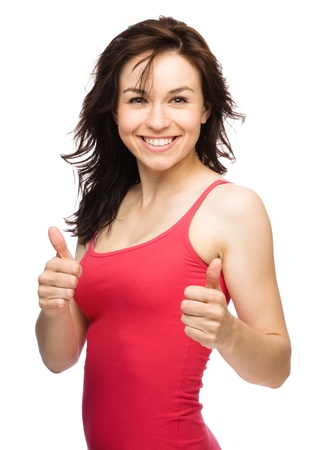 Young woman dressed in red is showing thumb up gesture using both hands, isolated over white