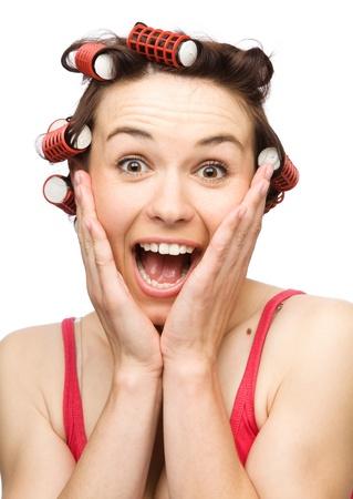 éxtasis: Mujer joven está sosteniendo su cara de asombro mientras llevaba el cabello, rodillos, aislado más de blanco Foto de archivo