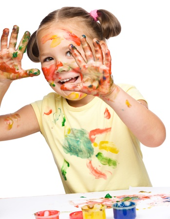 Portrait of a cute cheerful girl playing with paints, isolated over white Stock Photo - 15929831