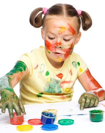 Portrait of a cute cheerful girl playing with paints, isolated over white Stock Photo - 15940433