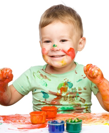 clenching: Portrait of a cute little boy playing with paints clenching his fists in joy, isolated over white Stock Photo