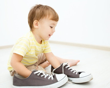 baby shoes: Cute little boy is playing with big sneakers while sitting on the floor